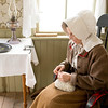 An interpreter in the Mary Hafford house takes advantage of the beautiful window light to knit.