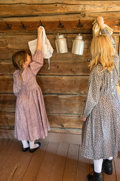 Girls hang up their bonnets upon entering the one room Raspberry schoolhouse.