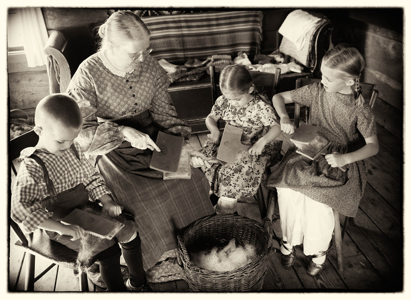 Children learn how to card wool at the Kvaale farm.