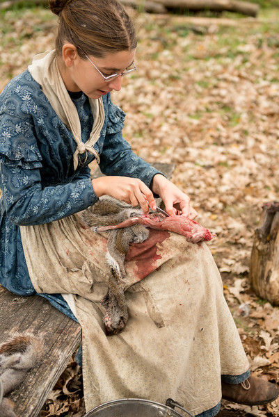 An interpreter butchers a squirrel at the Norwegian Fossebrekke farm.  Squirrels were an important source of meat in 19th century Wisconsin.