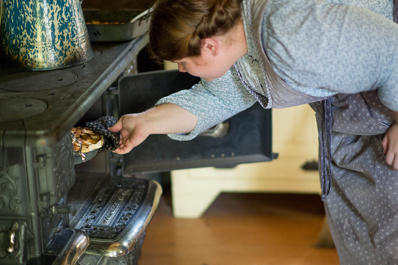 An interpreteer removes a pie from the wood cook stove oven at the Ketola farm.