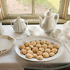 Mary Hafford, an Irish widow, baked cookies this morning and displays them with her finest tea set.