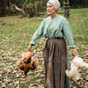 An interpreter at the Ketola farm carries chickens which she will feather and butcher.