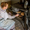An interpreter puts pies in the oven of the cast iron stove at the Koepsell farm.