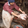 A farmer at the Ketola farm cleans and prepares a chicken for cooking.