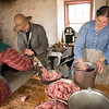 Grinding pork for making sausage in the Schottler farm summer kitchen.