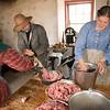 Grinding pork for making sausage in the Schottler farm summer kitchen.