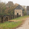 An interpreter walks out to the barn at the Schultz farm on a dreary rainy day.