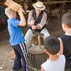 Young visitors practice splitting wood for kindling at the Koepsell farm in the German area.