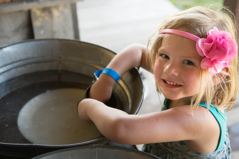 A young visitor helps wash dishes on the back porch of the Koepsell farmhouse.