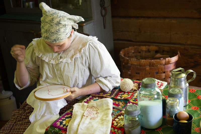 An interpreter works on her enbroidery in the kitchen of the Ketola house in the Finnish area of Old World.