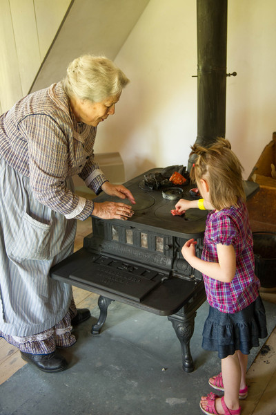 An interpreter helps a young visitor apply lamp black to to the iron cookstove in the Sisel Shoe shop.