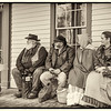 Interpreters wait for their morning briefing on the front porch of Four Mile Inn in Crossroads village.