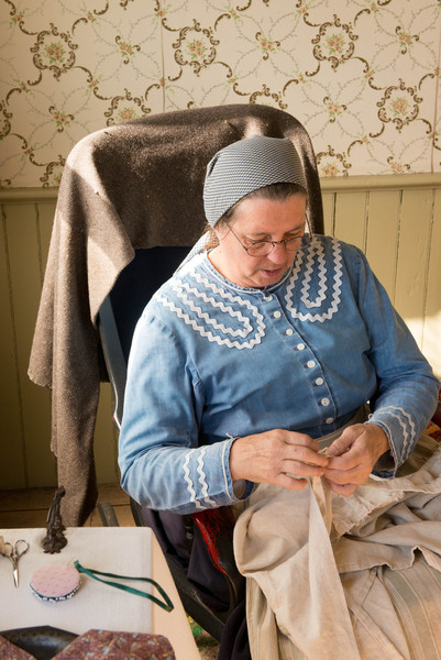 Mending clothes at the Mary Hafford house in Crossroads village.