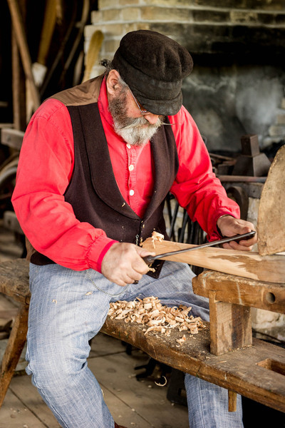 A blacksmith demonstrates use of a Schnitzelbank (wood shaver) in the Grotelueschen blacksmith shop in Old World Wisconsin.