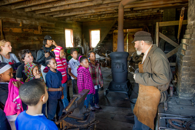 A blacksmith talks to a group of schoolchildren in the Viollage area of Old World Wisconsin.