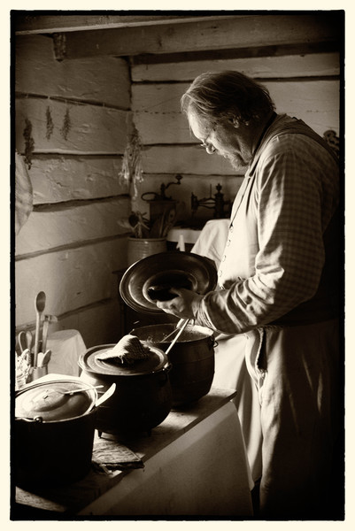An interpreter prepares food in the kitchen of the Kvaale farmhouse.