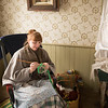 An interpreter crochets in the Mary Hafford house in Crossroads village.