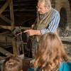 A blacksmith demonstrates his skills in the Grotelueschen blacksmith shop in Crossroads village.
