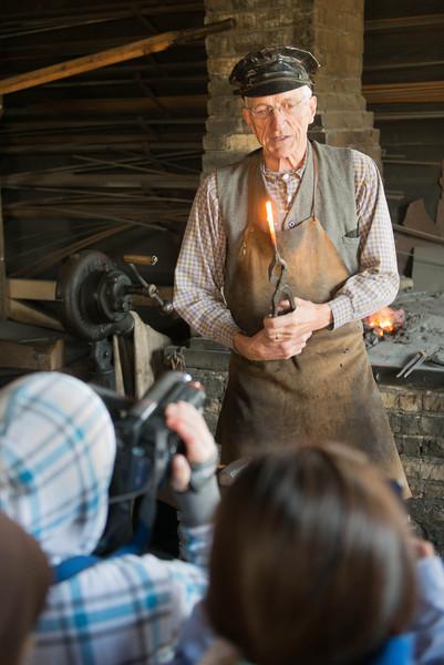 A blacksmith at the Groteleuschen blacksmith shop in Crossroads village demonstrates his skills to a group of schoolchildren.