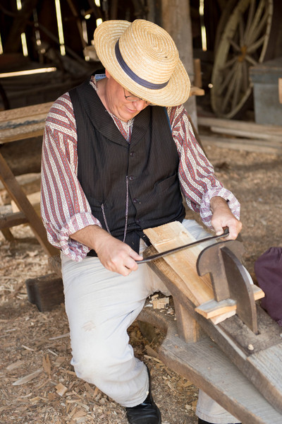 A farmer demonstrates use of a schnitzelbank or shaving horse in the woodworking shop of the Koepssell farm.