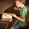 A young visitor intently studies a McGuffy reader in the Raspberry schoolhouse in the Norwegian area.