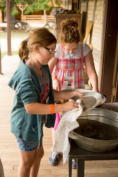 Young visitors at the Koepsell farm learn how dishes were washed in the 19th century.