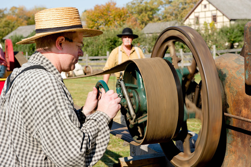 Adjusting one of the pulleys on equipment used at the early 20th century sawmill