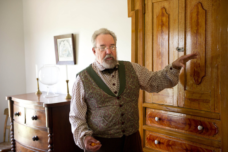 An interpreter points out features of the Sanford House to visitors