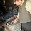 """Measuring the circumference of an iron """"tire"""" in the blacksmith shop before mounting it on a wagon wheel"""
