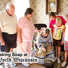 A family of vistors watch as an interpreter makes soap at Mary Hafford House in Crossroads Village
