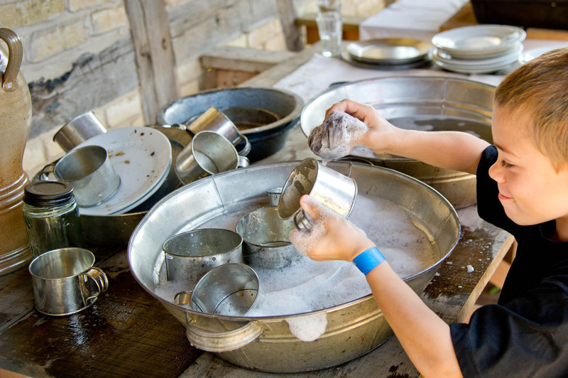 A young visitor enthusiastically helps wash dishes after the farm dinner for volunteers at the Koepsell Farm