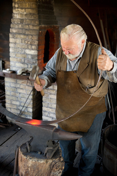"""Preparing an iron """"tire"""" for mounting on a wagon wheel in the blacksmith shop"""