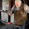 "Preparing an iron ""tire"" for mounting on a wagon wheel in the blacksmith shop"