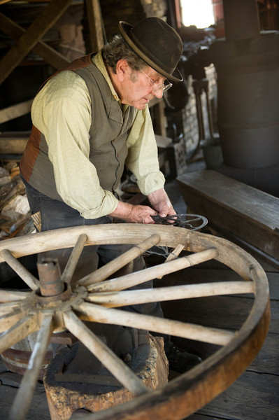 "Measuring the circumference of an iron ""tire"" in the blacksmith shop before mounting it on a wagon wheel"