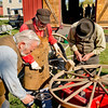 Blacksmiths carefully measure an iron tire prior to mounting it on a wagon wheel.