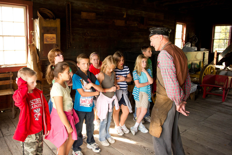 A blacksmith talks to a group of schoolchildren in the Grotelueschen Blacksmith Shop in Crossroads Village