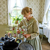 An interpreter prepares dinner in the Mary Hafford House in Crossroads Village