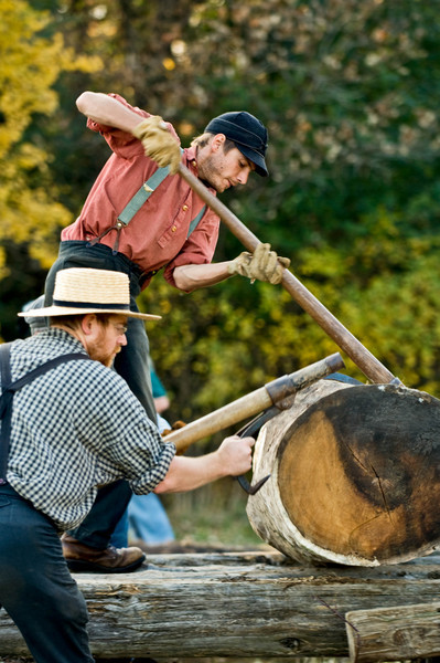 Old World farmers load a log onto the portable steam powered sawmill at the Autumn on the Farms special event held each October.