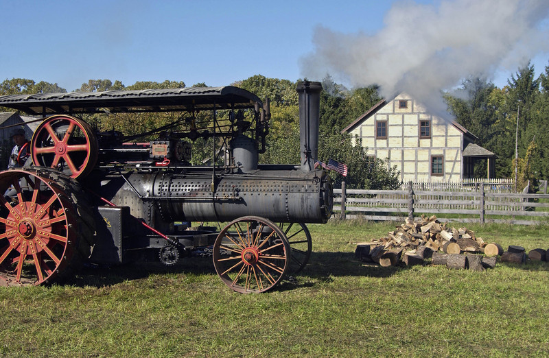 Steam engine used to power the portable saw mill at the annual special event, Autumn on the Farms, in  October.  Koepsell farmhouse is in the background.