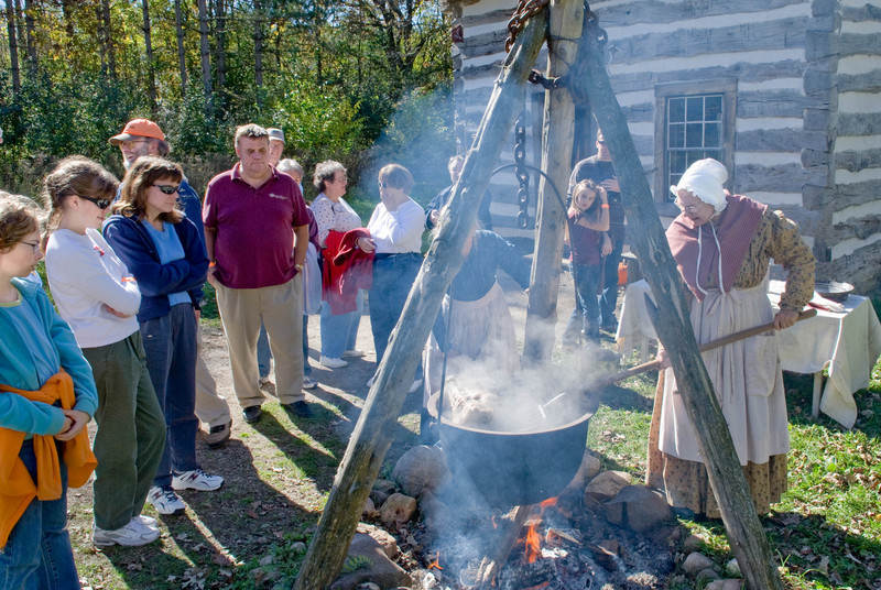 An interpreter makes head cheese in the kettle outside the cabin at the 1845 Fossebrekke farm.