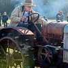 A farmer fires up an early 20th century tractor at the Autumn on the Farms special event.
