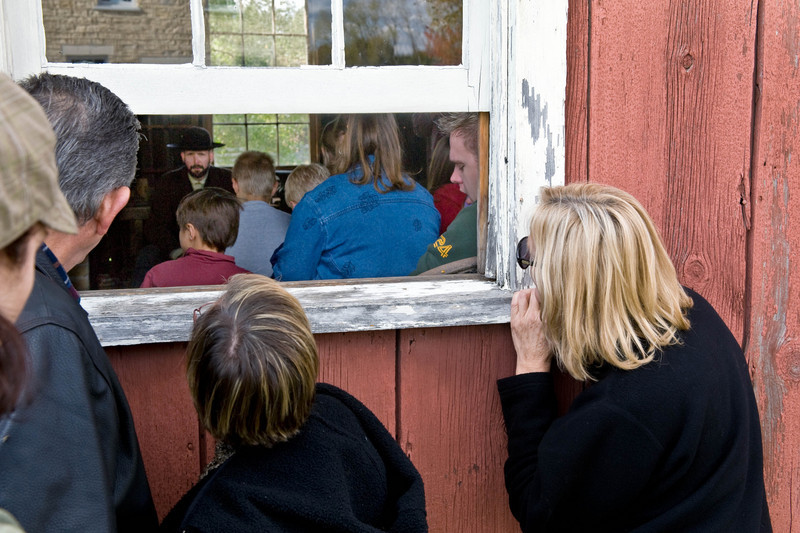 Visitors peer in the window of the Peterson Wagon shop in Crossroads village to catch a glimpse of a skit about the devastating 1871 fire in Peshtigo, WI.