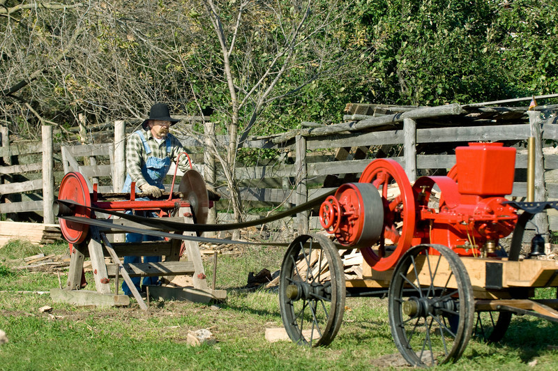 An early 20th century portable gasoline engine drives a circular saw used to cut firewood at the annual Autumn on the Farms special event.