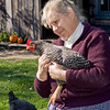 Jane, an interpreter, making friends with a chicken at the Ketola farm,