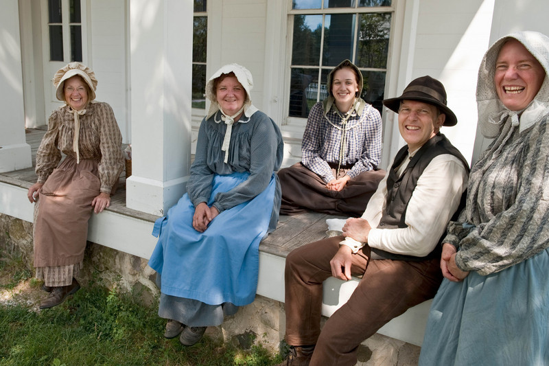 Marcia (far left), historic gardener, takes a break with some of her volunteers on the porch of the 1860 Sanford House in Crossroads Village.