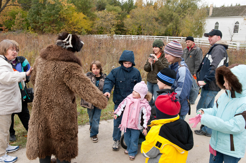 """Prairie Bob,"" dressed in his buffalo skin coat and skunk cap, greets visitors in Crossroads Village as they enter the museum."