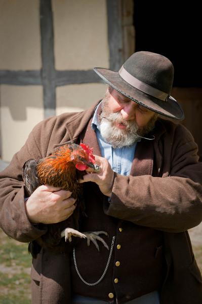 Richard, an interpreter and historic farmer, befriends a chicken at the 1860 Schulz (German) farm.