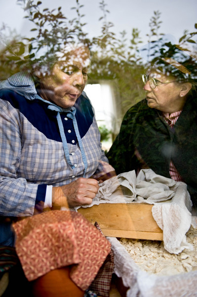 Two interpreters having a heated discussion are seen through a window in the Mary Hafford house in Crossroads Village.