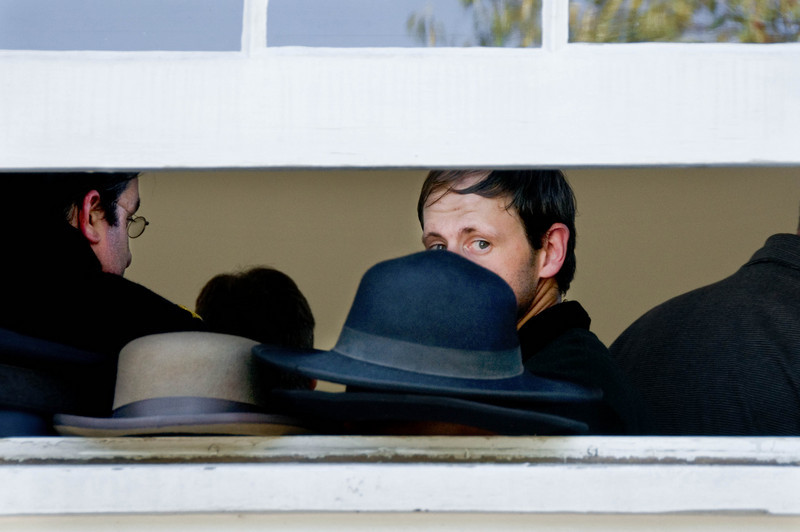 Civil War reenactors  attending the wedding of a fellow reenactor peer out the window of St. Peter's church in Crossroads Village on a hot summer day.